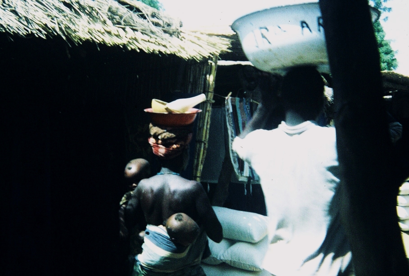 In African market. Back of African man in white shirt walking ahead, head-bearing large white pan; back of African woman with bare shiny ebony skin, young child in her arms, an infant strapped on her back, and head-bearing a small bowl and bottle in a larger bowl.